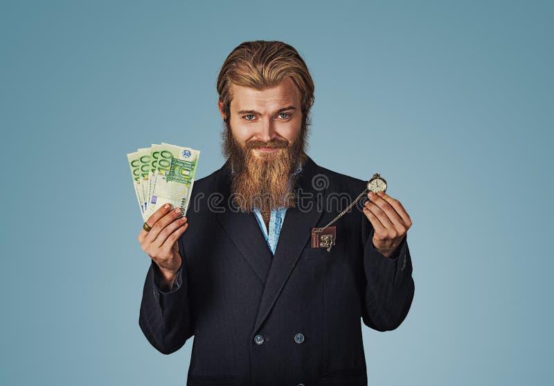 Kerl ist ein glücklicher Sieger, der einen Stapel des Geldes und der Uhr hält stockfotografie