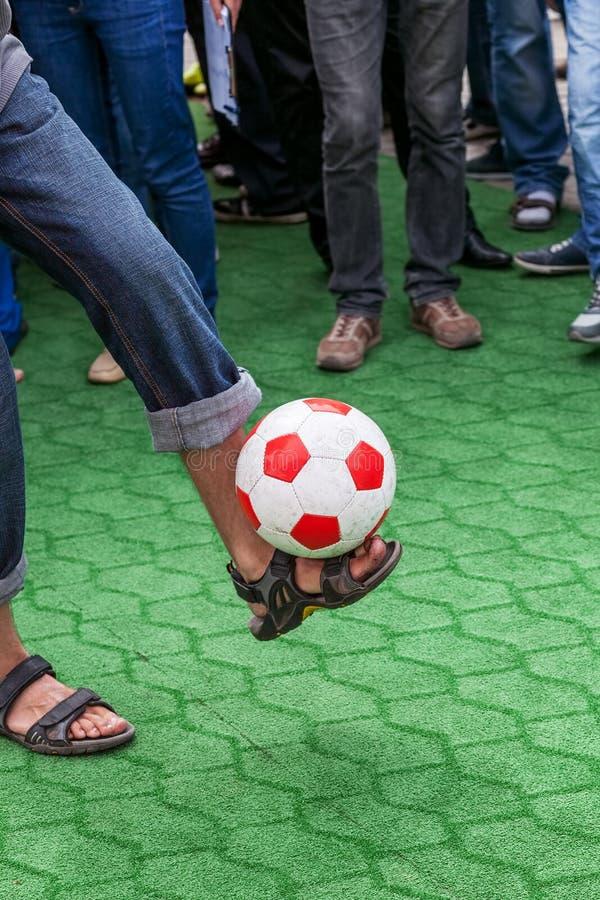 Kerl jongliert mit einem Fußball lizenzfreies stockbild