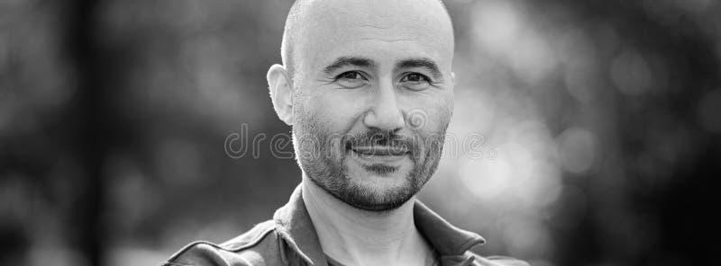 Kerl lächelt Einfarbiges Porträt eines kahlen bärtigen Mannes lizenzfreie stockfotografie