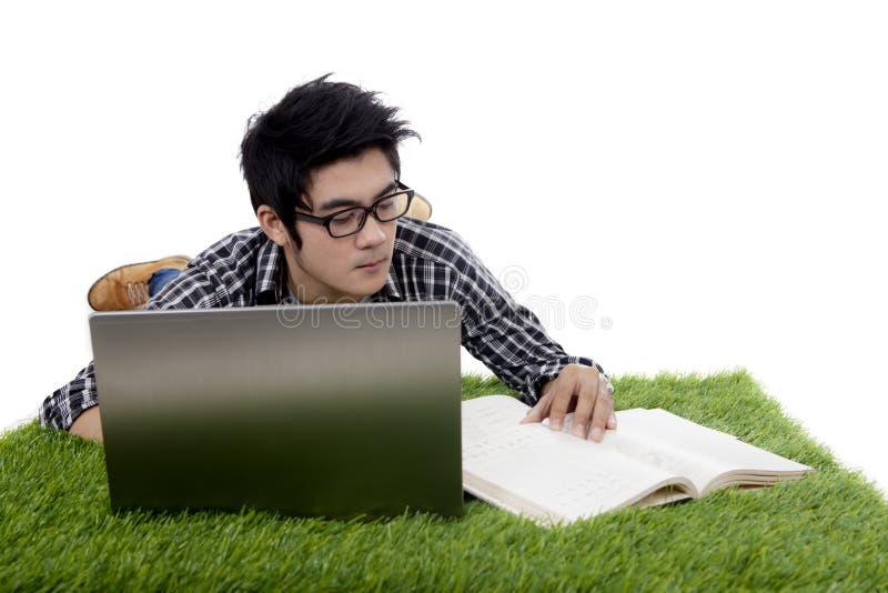 Kerl liest Buch bei der Anwendung des Laptops auf Gras stockfotografie
