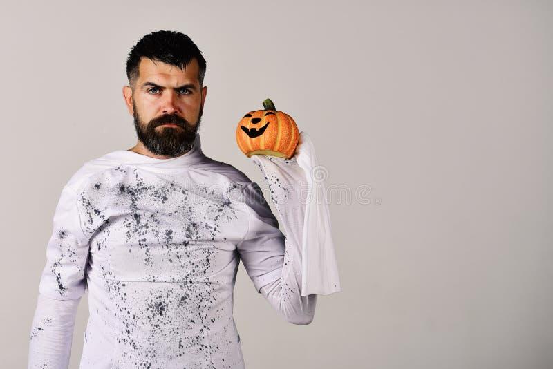 Kerl mit Bart hält orange Laterne der Steckfassung O Halloween-, Kultur- und Traditionskonzept Mann mit ernstem Gesicht stockbild