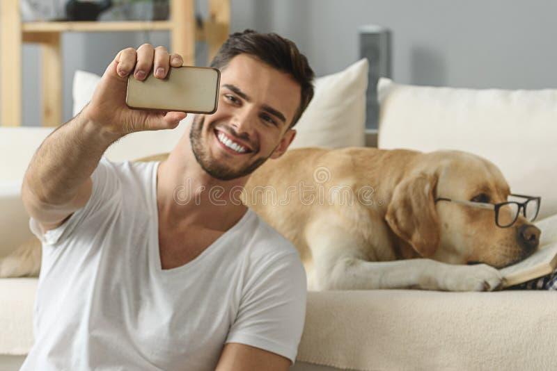 Kerl mit dem Smartphone, der Fotos von einem Labrador macht stockfoto