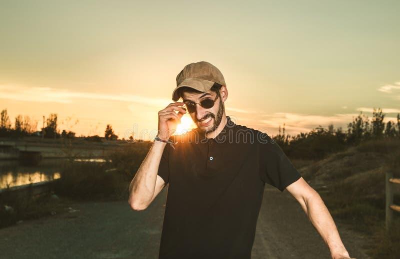 Kerl mit den Gläsern und Kappe, welche die Kamera betrachten stockbilder