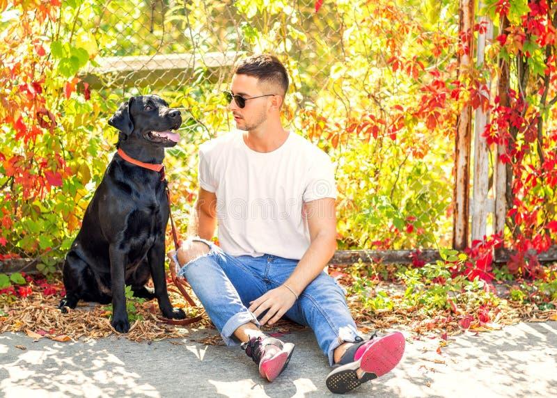 Kerl mit einem Hund geht in einen Park im Herbst stockfotografie