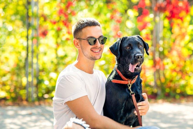 Kerl mit einem Hund geht in einen Park im Herbst stockfoto