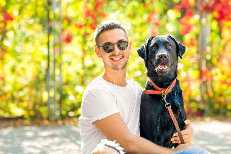 Kerl mit einem Hund geht in einen Park im Herbst lizenzfreie stockbilder