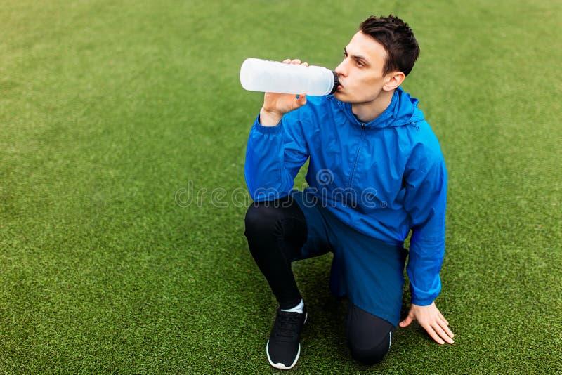 Kerl nach Übung, Trinkwasser auf dem Fußballplatz Porträt des schönen Kerls in der Sportkleidung lizenzfreies stockbild