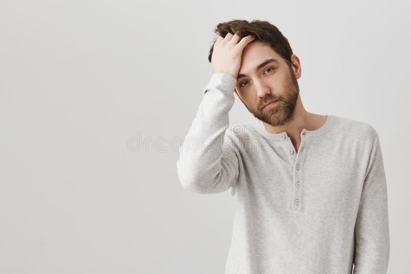 Kerl schaut im Spiegel und fühlt sich heute sexy Porträt der schönen europäischen männlichen haltenen Hand auf Haar und Stellung  stockfoto