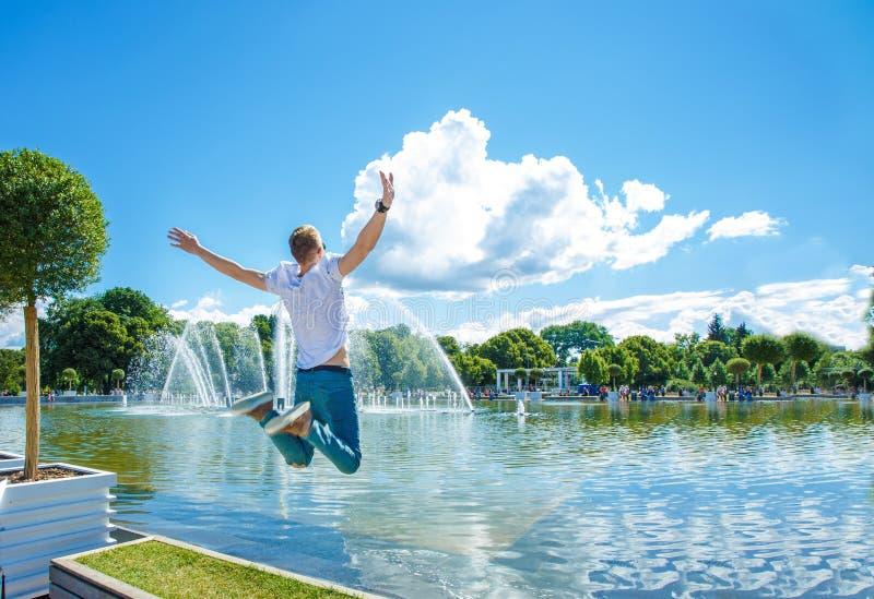 Kerl schwebt in der Luft Der Kerl schwebt in der Luft vor dem hintergrund eines Brunnens lizenzfreie stockfotos