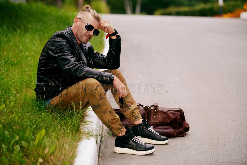 Kerl sitzt auf Rasen stockbilder