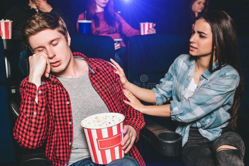 Kerl sitzt im Stuhl und im Schlafen Er langweilt sich und ermüdet Seine Freundin versucht, ihn oben aufzuwecken stockfoto