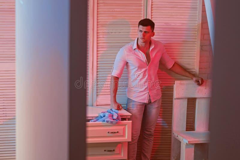 Kerl tun Wäschereihausarbeit im Haushalt Mannstand im Rauminnenraum mit Möbeldesign Sexy Macho im Hemd und in den Jeans lizenzfreies stockbild