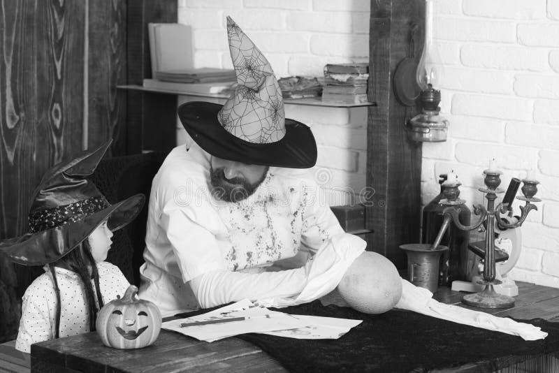 Kerl und Junge auf hölzernem und weißem Ziegelsteinhintergrund Witcher und kleiner Magier machen Dekor für Halloween lizenzfreies stockbild