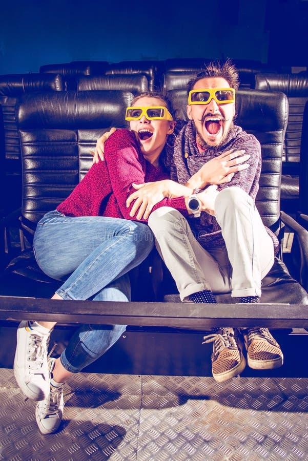Kerl- und Mädchen3d Gläser sind beim Aufpassen eines Films in einem Kino sehr besorgt lizenzfreie stockbilder