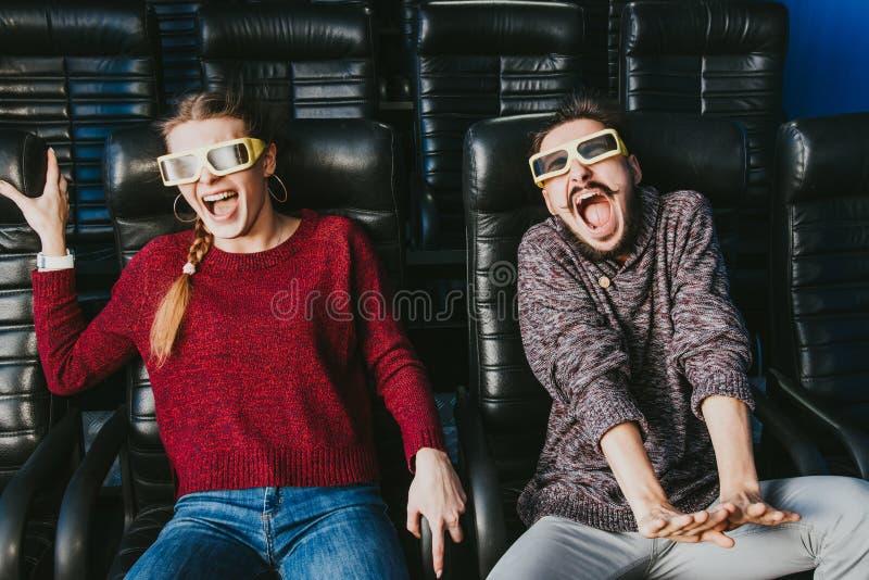 Kerl- und Mädchen3d Gläser sind beim Aufpassen eines Films sehr besorgt stockbild