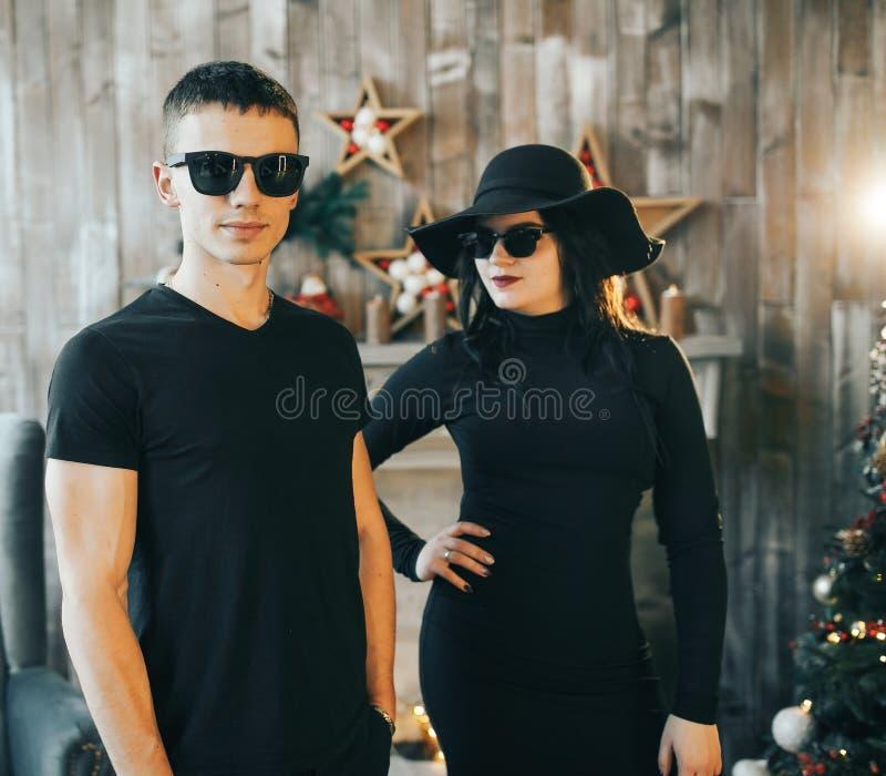 Kerl und Mädchen, die vor einem Kamin nahe einem Weihnachtsbaum stehen stockfotografie