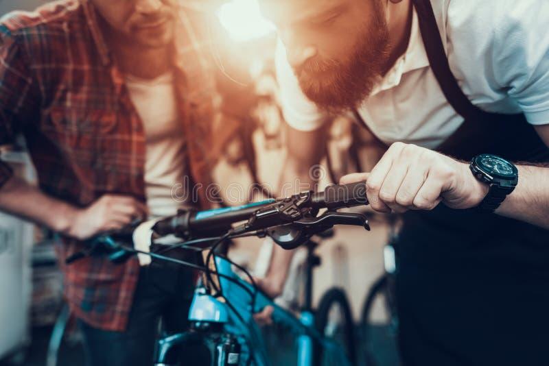 Kerl und Schlosser Fixes Bicycle im Sport-Speicher stockbild