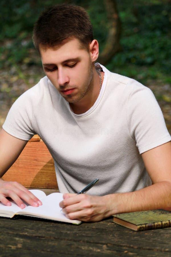 Kerl und Student nimmt Kenntnisse im Notizbuch und lernt und schreibt Gedanken, schreibt das Buch, er vorbereitet seine Schlusspr lizenzfreie stockfotos