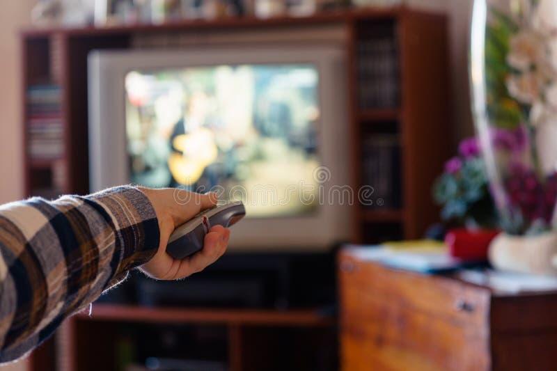 Kerl zapping im seinem alten Fernsehen lizenzfreie stockfotografie