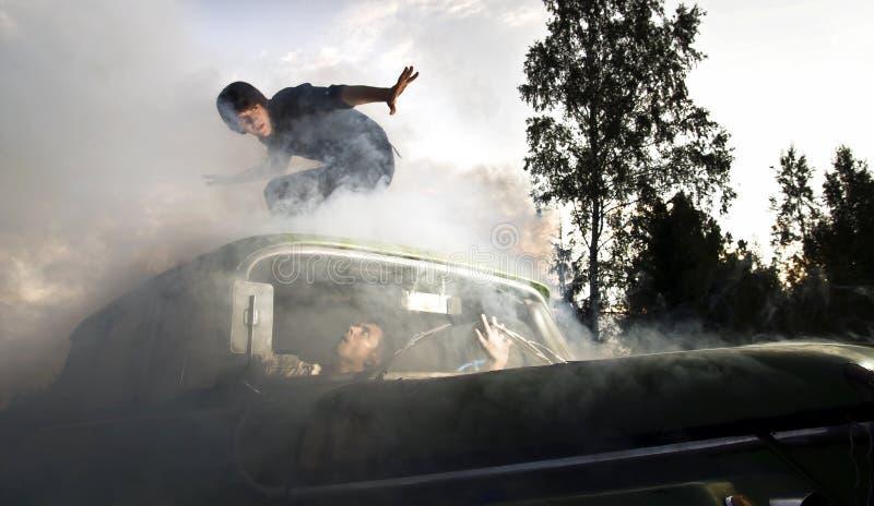 Kerle im Auto voll des Rauches stockbild