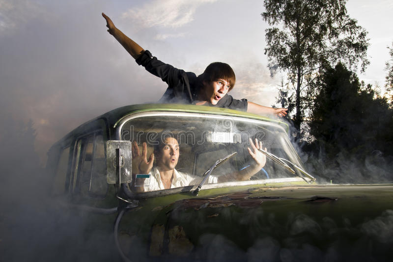 Kerle im Auto voll des Rauches lizenzfreie stockfotos