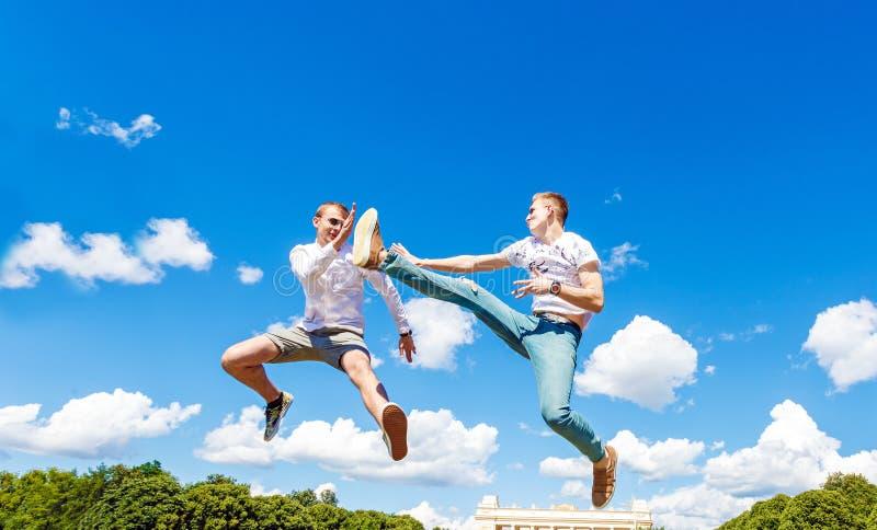 Kerle kämpfen in der Luft Kerle springen in Luft und treten seinen Freund Kerle kämpfen in der Luft gegen stockbild