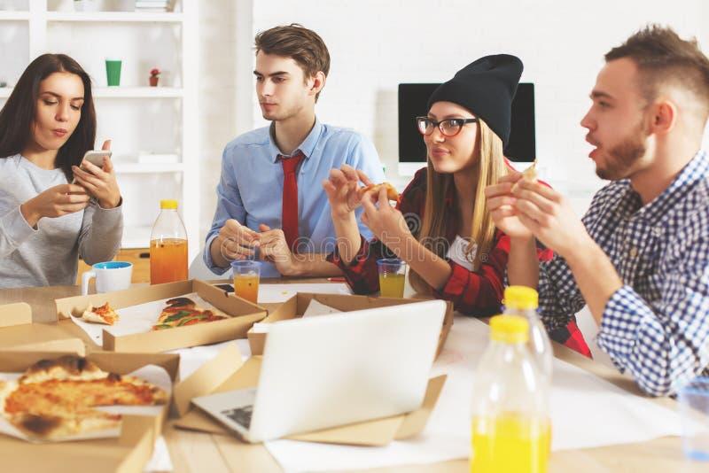 Kerle und Mädchen, die am Arbeitsplatz essen lizenzfreies stockfoto