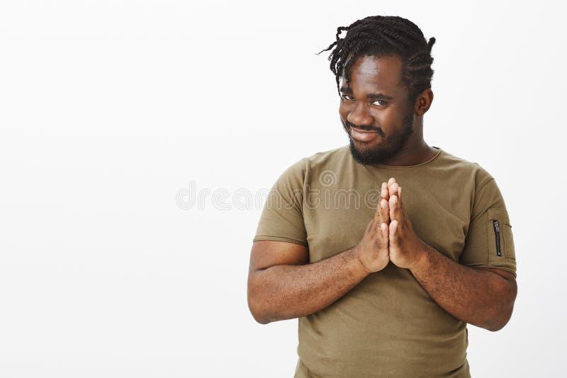 Kerlreibungspalmen, bösen schlechten Plan habend Intrigierter lustiger Afroamerikanermann im olivgrünen T-Shirt, Händchenhalten b lizenzfreie stockfotografie