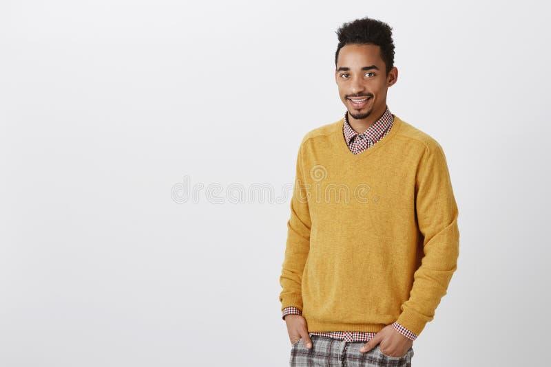 Kerlträume, zum berühmter Doktor zu werden Freundlicher schöner gewöhnlicher Afroamerikanerstudent in der gelben Pulloverholding stockfoto