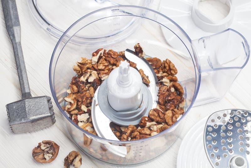 Kernwalnüsse in einer Küchenmaschine bereit zerquetscht zu werden lizenzfreie stockfotos