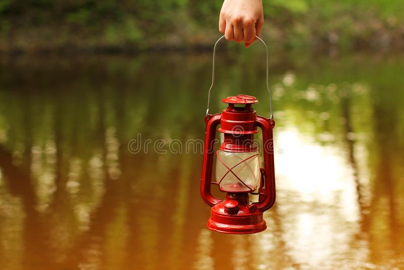 Kerosene lamp in hand against the background of the river stock photos
