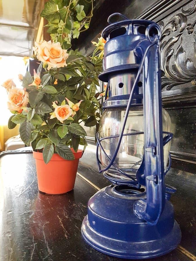 Kerosene lamp and rose on black piano royalty free stock photos
