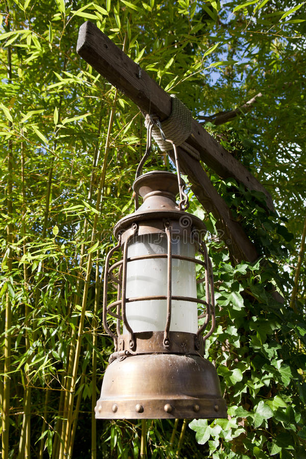 Kerosene oil lamp is hung up on leaves background. Street aged vintage copper kerosene oil lamp with glass bulb is hung up batten outside on the green leaves royalty free stock photos