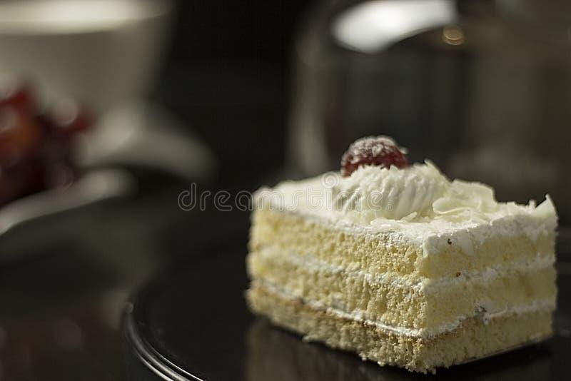 Kers bovenop cake met een elegante vage achtergrond stock foto