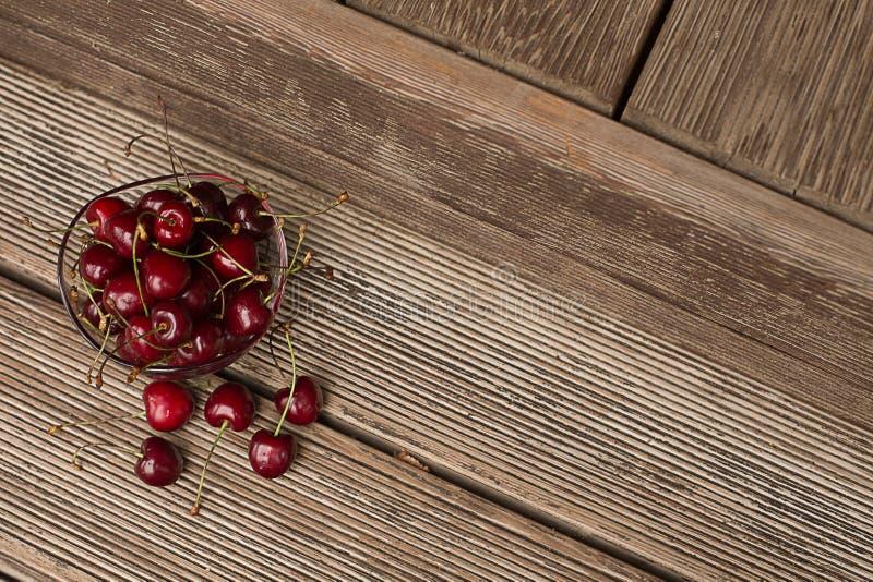 Kers in een kom op een houten achtergrond stock afbeeldingen