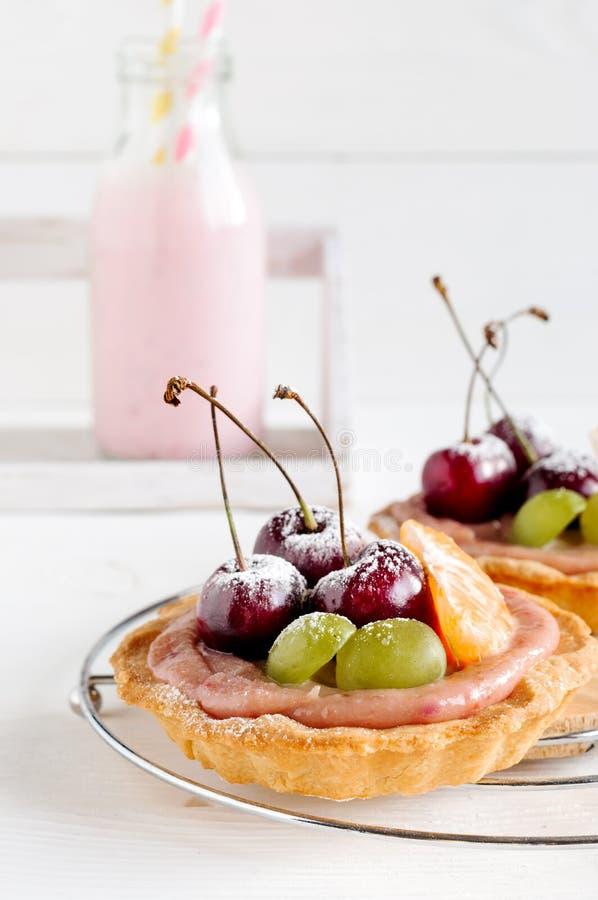 Kersen minitaartjes met vruchten en melk royalty-vrije stock afbeeldingen