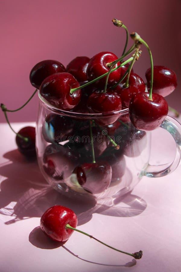 Kersen in transparante kom, roze achtergrond Rode kers Verse kersen Gezond voedselconcept stock foto's
