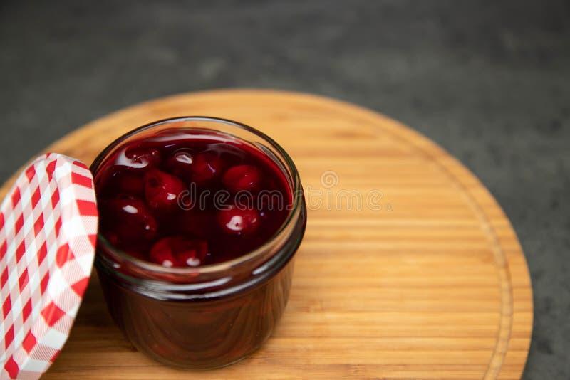 Kersenjam in een glaskruik met een open deksel van rode en witte kleur op een houten raad, een raad Grijze achtergrond Plaats voo royalty-vrije stock afbeeldingen