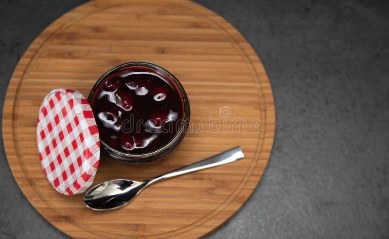 Kersenjam, kersengelei in een glaskruik met een open rood en wit deksel die zich naast het bevinden De jam op een houten plaat, n stock fotografie