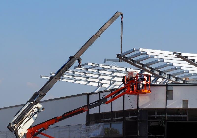 Kersenplukker en een telescopische kraan op het werk voor de installatie van dak metaalkader op een nieuw gebouw stock afbeeldingen