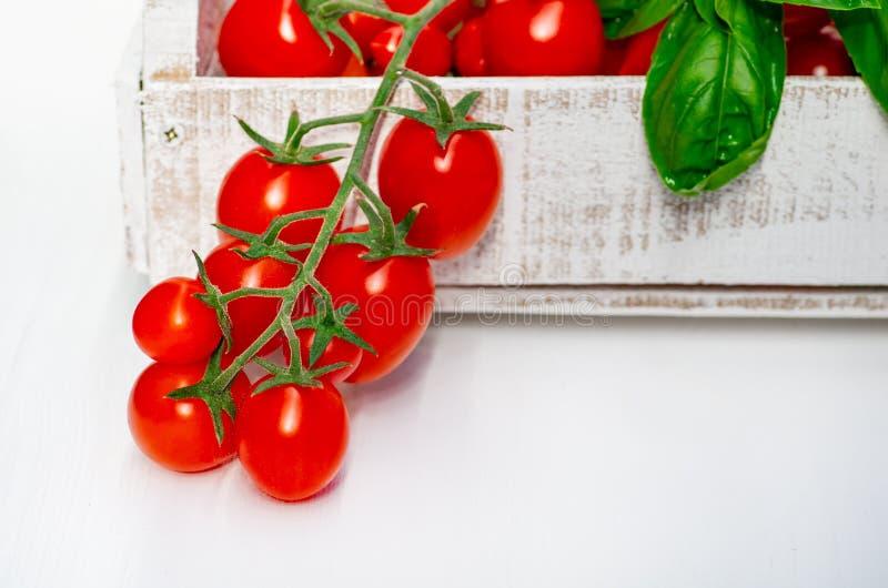 Kersentomaten op een tak in een houten doos op een witte achtergrond Het plukken tomaten stock fotografie