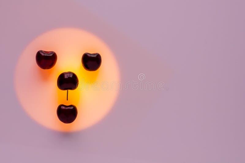 Kersenvruchten gezet op oranje die kleurenlicht als gelukgezicht wordt geplaatst stock fotografie