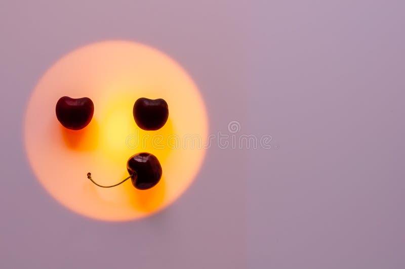Kersenvruchten gezet op oranje die kleurenlicht als het glimlachen gezicht wordt geplaatst royalty-vrije stock afbeelding