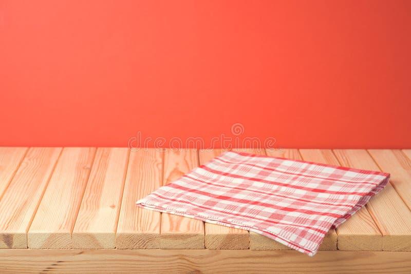 Kerst lege houten tafel met tafelkleed over rode feestelijke achtergrond royalty-vrije stock afbeelding