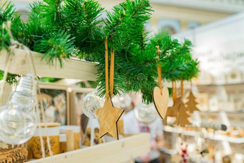 Kerstaire decoratie Houten speelgoed van verschillende vormen, sterren, hart, pelsbomen die aan de pelsboomtak hangen stock foto's