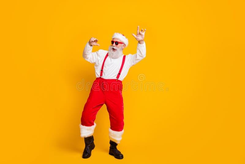 Kerstavond is hard kletsen Volledige foto van de coole, funky santa claus hipster in het rood, die geniet van de traditie van een royalty-vrije stock afbeelding