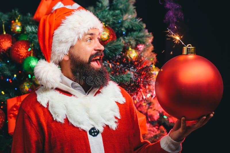 kerstbom kerstverrassing De kerstman houdt een stuk speelgoed vast voor de kerstboom in de vorm van een bom royalty-vrije stock foto