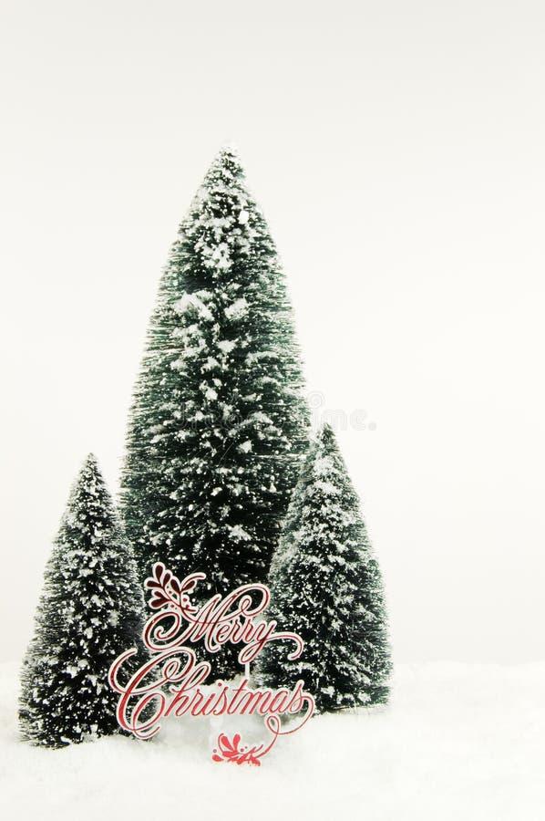 Kerstbomen en Vrolijk Kerstmisteken in Sneeuw stock afbeelding