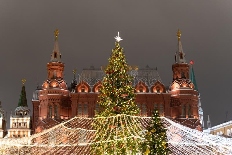 Kerstboom dicht bij de Russische bouw van het Geschiedenismuseum, het Rode Vierkant en het Kremlin in Moskou tijdens het seizoen  stock foto's