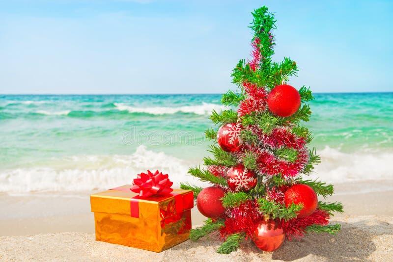 Kerstboom en gouden gift met grote rode boog op het overzeese strand stock foto
